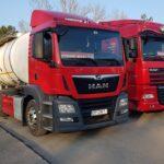 dwie czerwone ciężarówki z białymi cysternami