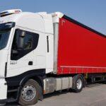biała ciężarówka z czerwoną naczepą